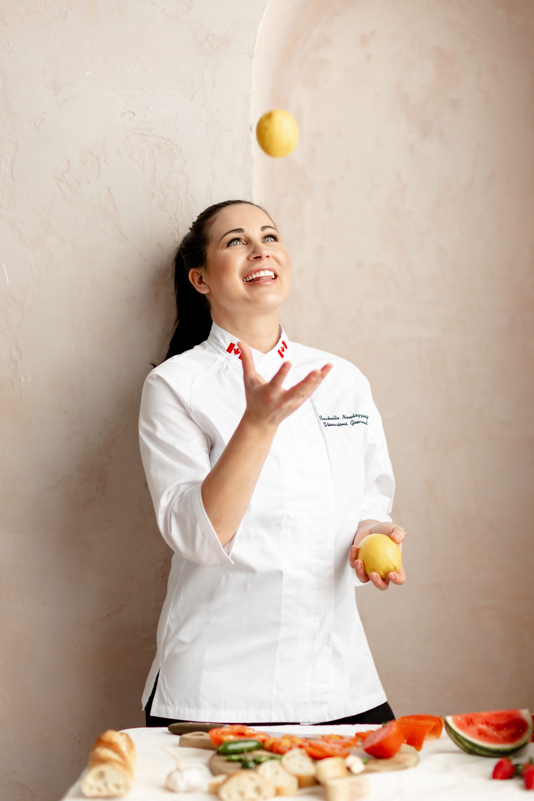 Rachelle is a food blogger in a chef's jacket tossing a lemon in the air