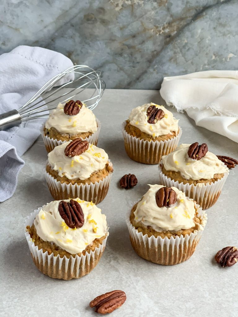Carrot Cake Muffins with Cream Cheese Frosting and lemon zest with a pecan on top