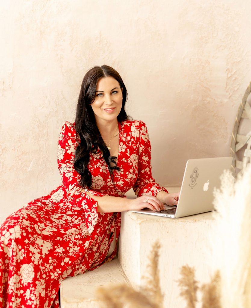 Vivcaious Gouremt ina dress on a laptop computer